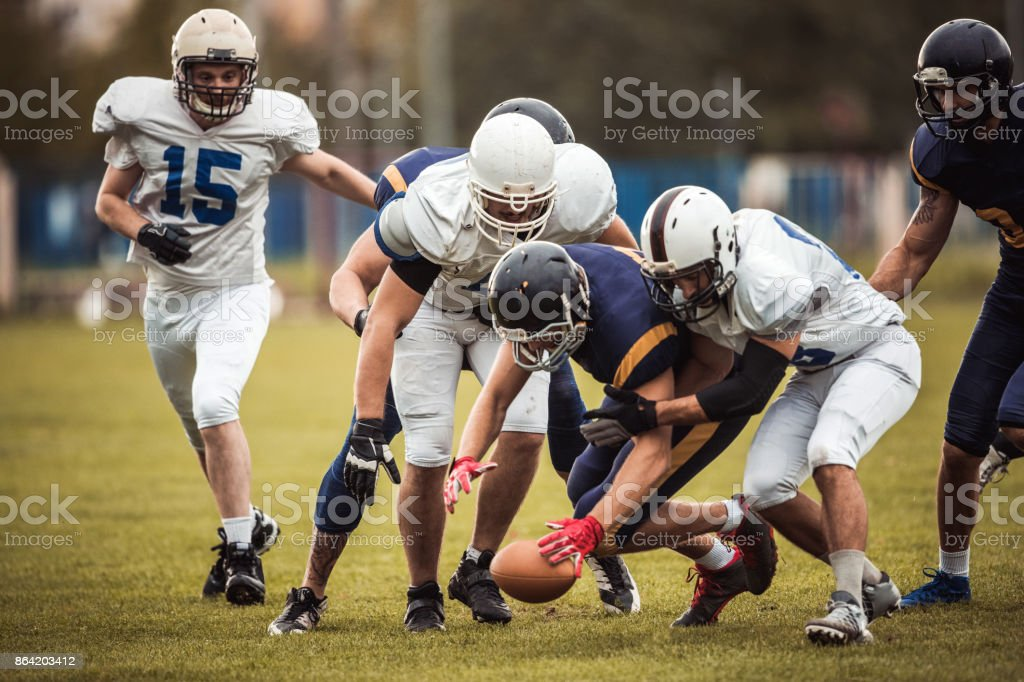 Large group of American football players in action during the match. royalty-free stock photo