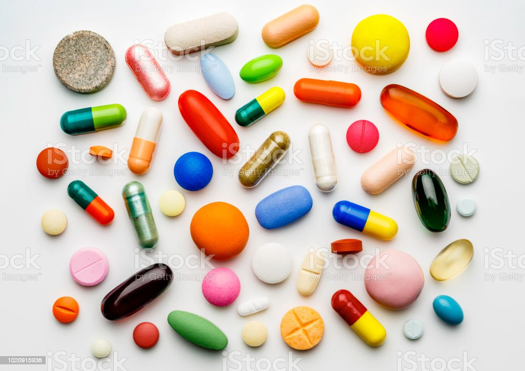 Large group of assorted capsules and pills on white background stock photo