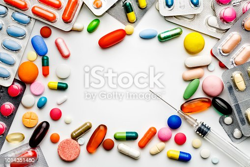 Health themes. Large group of assorted capsules, pills and blisters making a frame on white background. Space for text.