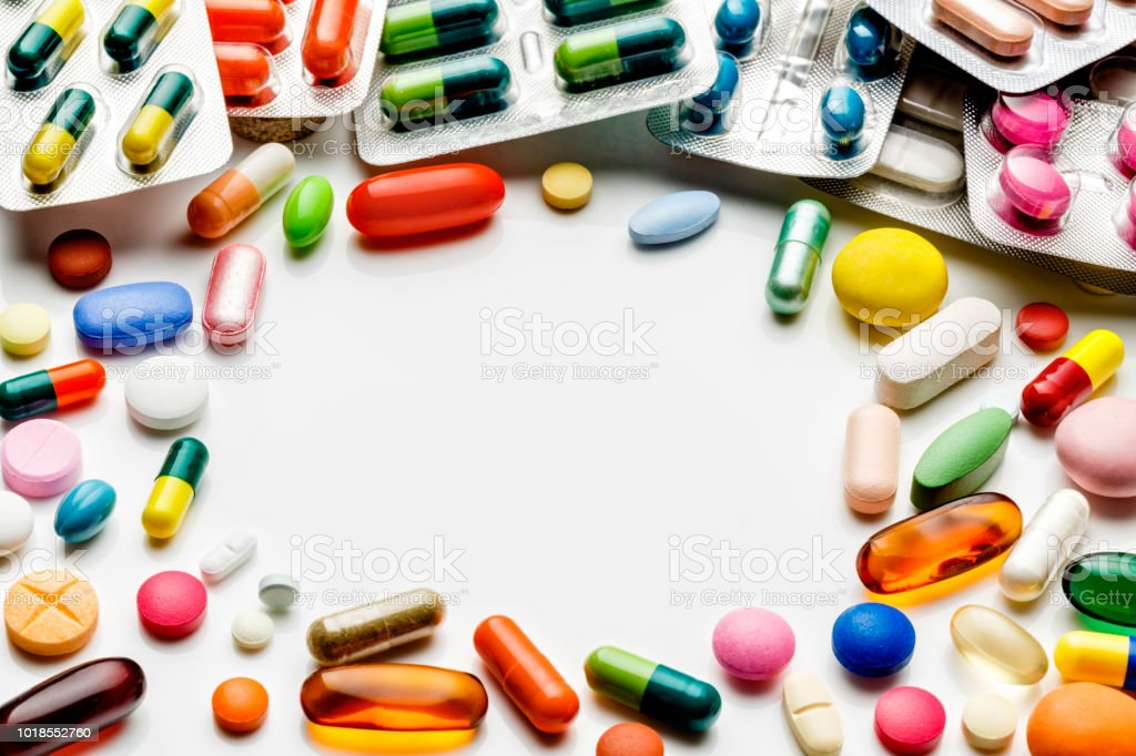 Large group of assorted capsules, pills and blisters making a frame on white background stock photo