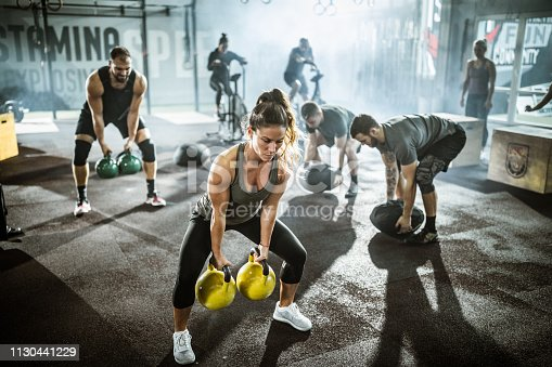 Large group of athletic people having training in a gym. Focus is on woman with kettle bells.