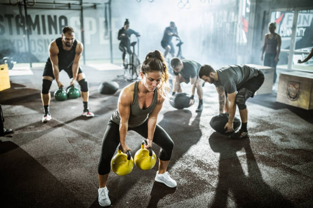 Large group of athletes exercising strength of cross training in a gym. stock photo