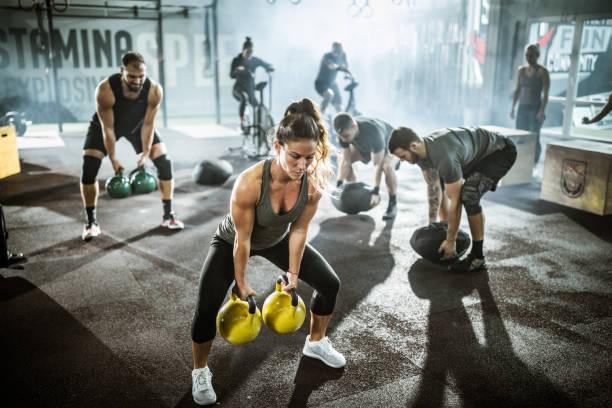 Große Gruppe von Athleten, die Stärke der cross-Training in einem Fitnessstudio trainieren. – Foto