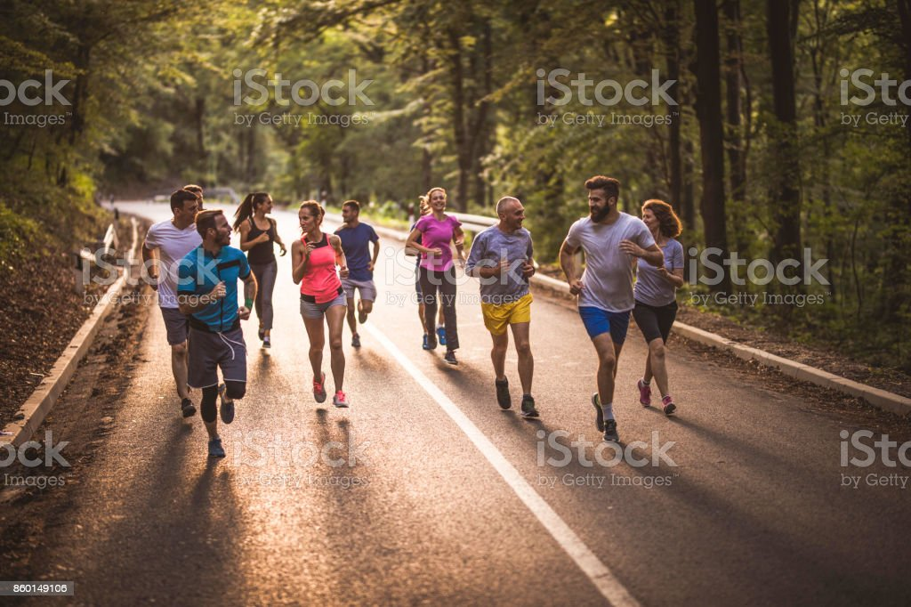 Large group of athletes having a road running race and talking. stock photo
