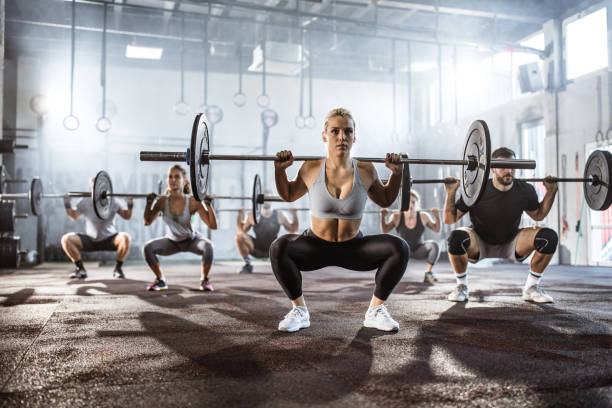 Large group of athletes having weight training in a gym. stock photo