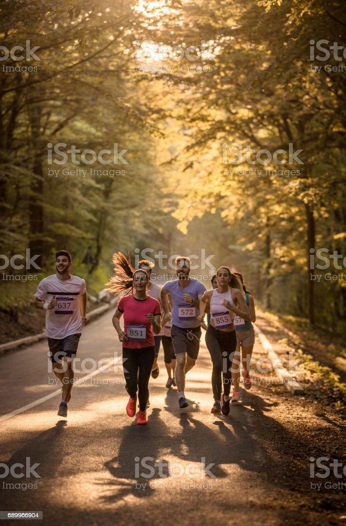 Grande grupo de pessoas atléticas correndo uma maratona pela floresta. - foto de acervo