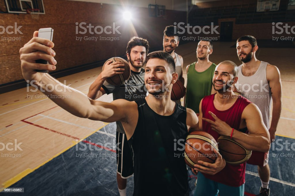 Large group of basketball players having fun while taking a selfie on the court. - Royalty-free Adult Stock Photo