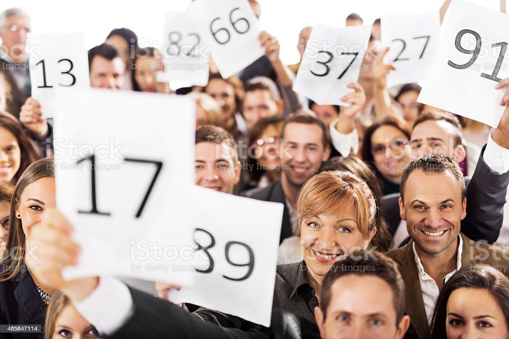 Large group of business people at an auction stock photo