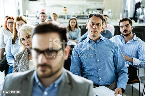 istock Large group of business people attending a training class in a board room. 1148380016