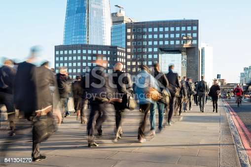 Blurred image of business commuters crossing London Bridge, office buildings with The Shard are visible in the background, London, England