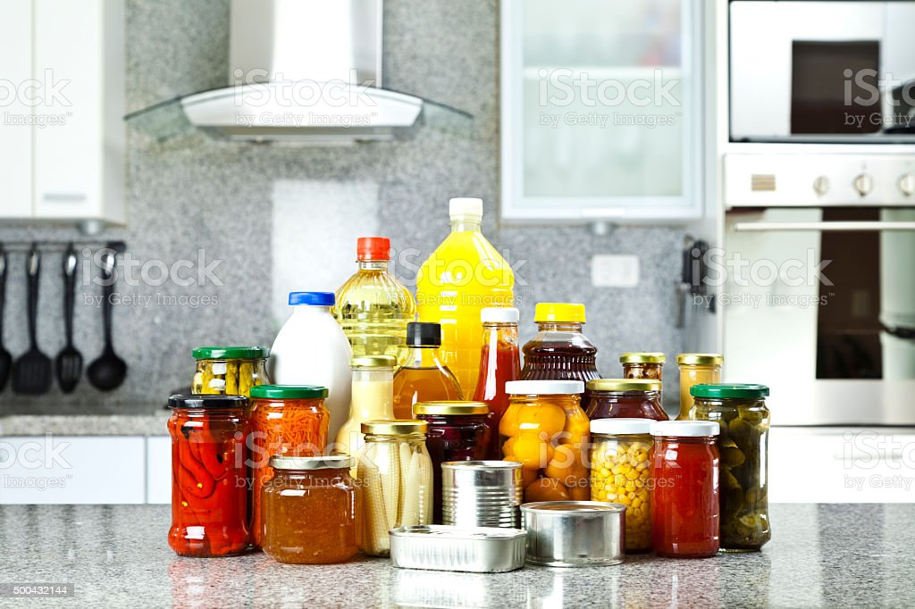 Large group of canned food on kitchen countertop stock photo