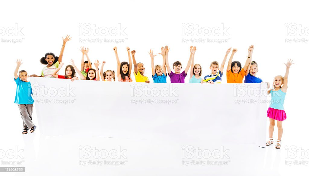 Large group of cheerful children holding white banner. stock photo