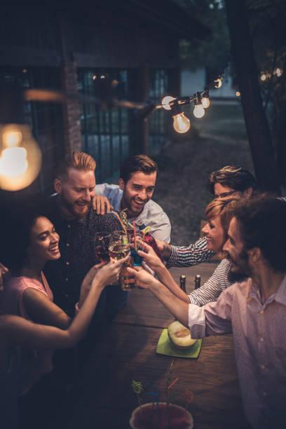 Große Gruppe von fröhlichen Menschen, die Spaß beim Toasten mit Alkohol auf einer Party Nacht. – Foto
