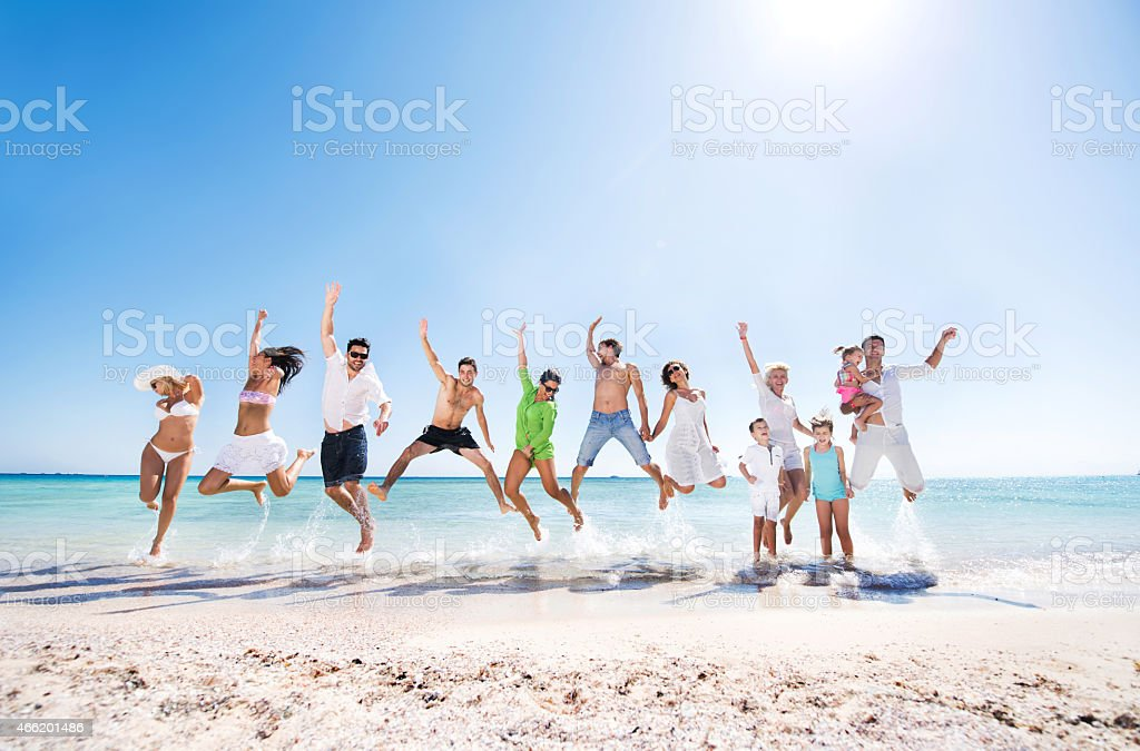 Large group of cheerful people jumping on the beach. stock photo