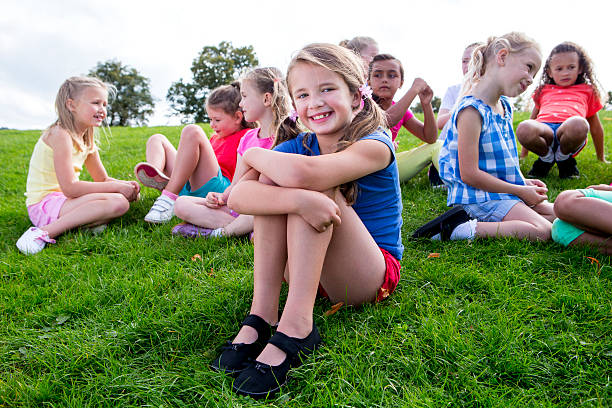 Large Group Of Children Sitting on the Grass stock photo