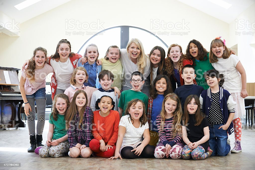 Large Group Of Children With Teacher Enjoying Drama Workshop Tog stock photo