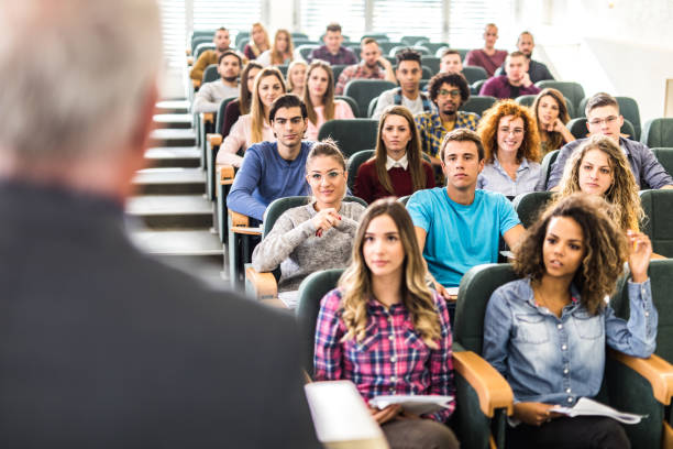 Large group of college students listening to their professor on a class. Large group of college students paying attention during a class in amphitheater. amphitheater stock pictures, royalty-free photos & images