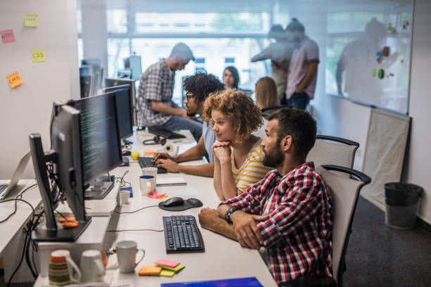 Large group of computer programmers working in the office. stock photo