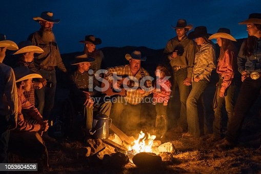 Large Group of cowboys and cowgirls together after a long outdoor day relaxing at the campfire together. Cowboy singing and playing guitar. Utah, USA.
