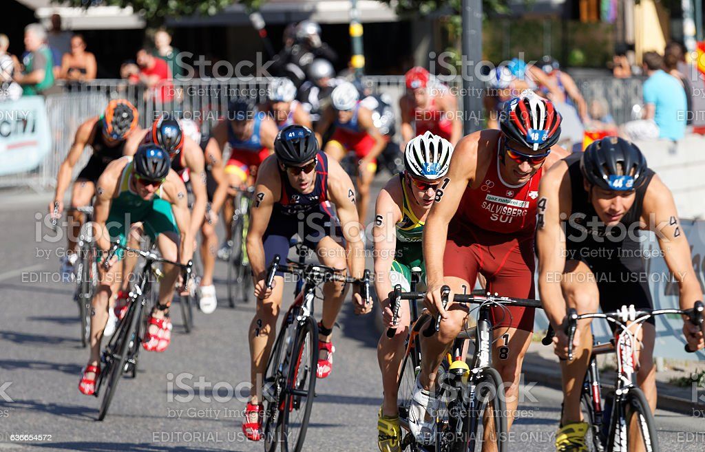 Large group of cycling triathlon competitors fighting stock photo