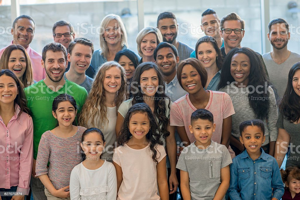 A multi-ethnic group of people are standing together in a room...