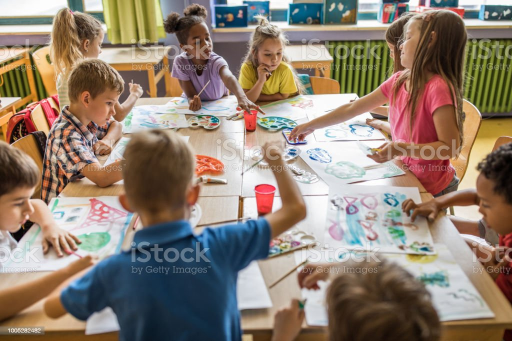 Large group of elementary students having an art class in the classroom. stock photo