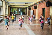istock Large group of elementary students running in the school hallway. 1038323414
