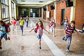 istock Large group of elementary students running in the school hallway. 1072966130