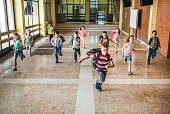 istock Large group of elementary students running in the school hallway. 984732362
