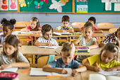 istock Large group of elementary students writing a dictation in the classroom. 1139436373