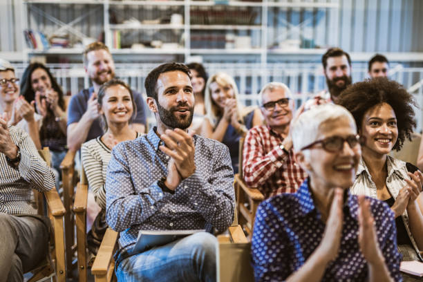 Large group of entrepreneurs applauding their colleague after seminar in board room. Crowd of happy freelancers congratulating public speaker on great business seminar in a board room. attending stock pictures, royalty-free photos & images