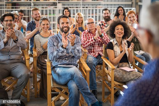 894290604 istock photo Large group of entrepreneurs applauding their colleague after seminar in board room. 874356854