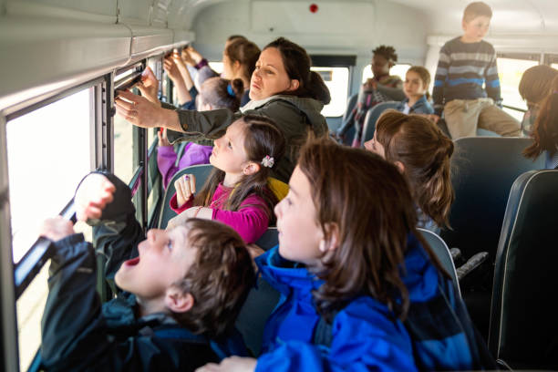 Large group of exited kids on school bus. Large group of elementary age exited school kids on a bus opening the window. Teacher is helping them. Horizontal waist up outdoors shot on a bright sunny day. Copy space. field trip stock pictures, royalty-free photos & images