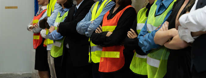 Large group of factory worker standing together in warehouse or storehouse . Logistics , supply chain and warehouse business concept .