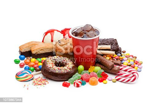 High angle view of a large group of multicolored products with high sugar level shot on white background. Food included in the composition are candies, donuts, chocolate bar, a glass of soda, ice cream, muffin and bakery items. High key DSRL studio photo taken with Canon EOS 5D Mk II and Canon EF 100mm f/2.8L Macro IS USM.