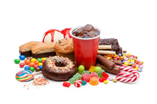 Large group of food with high sugar level isolated on white background High angle view of a large group of multicolored products with high sugar level shot on white background. Food included in the composition are candies, donuts, chocolate bar, a glass of soda, ice cream, muffin and bakery items. High key DSRL studio photo taken with Canon EOS 5D Mk II and Canon EF 100mm f/2.8L Macro IS USM. unhealthy eating stock pictures, royalty-free photos & images