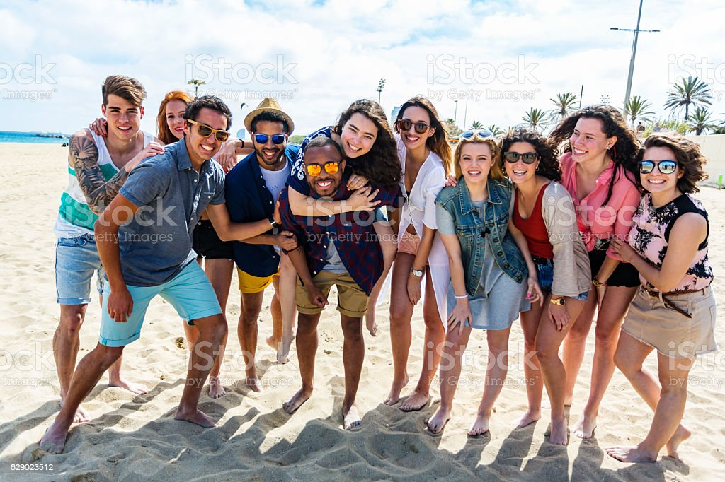 Large Group of Friends Having Fun on A Beach stock photo