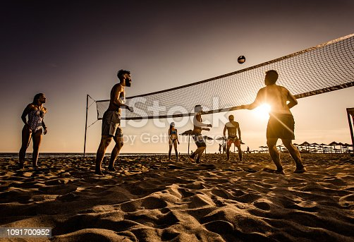 Young friends having fun while playing beach volleyball at sunset.