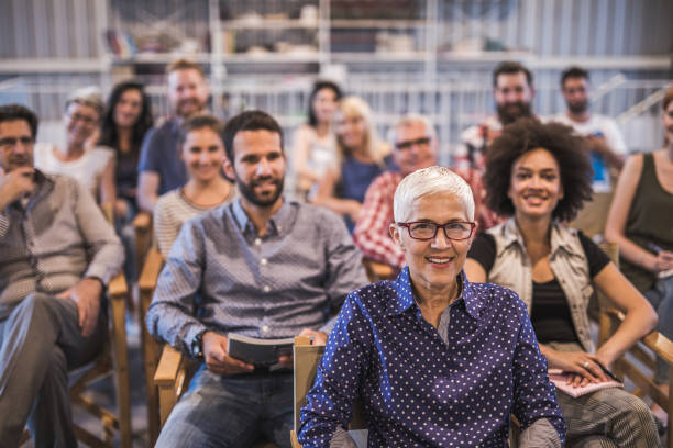 Large group of happy business people attending a seminar. stock photo