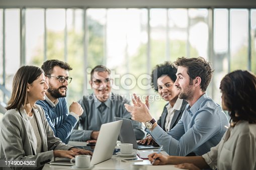 Happy business team talking on a meeting at conference table. Focus is on man talking.