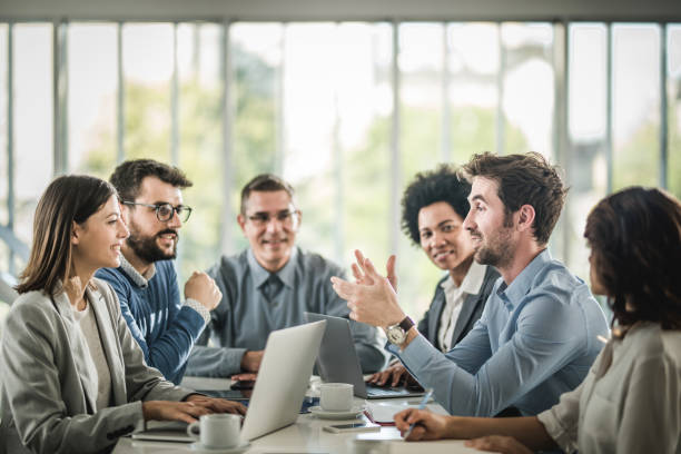 Large group of happy business people having a discussion on a meeting in the office. Happy business team talking on a meeting at conference table. Focus is on man talking. business meeting stock pictures, royalty-free photos & images