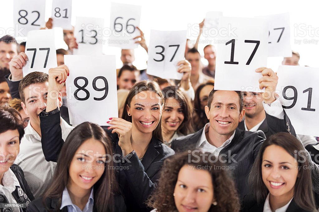 Large group of happy business people holding auction numbers. stock photo