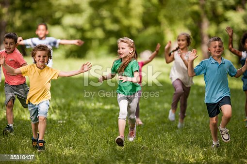 Group of happy kids having fun while running in spring day at the park.