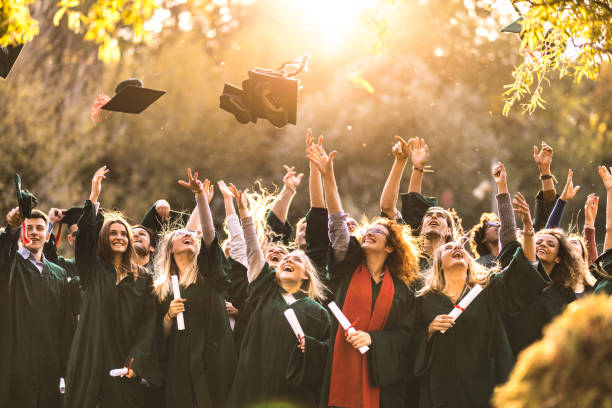 Large group of happy college students celebrating their graduation day outdoors. stock photo