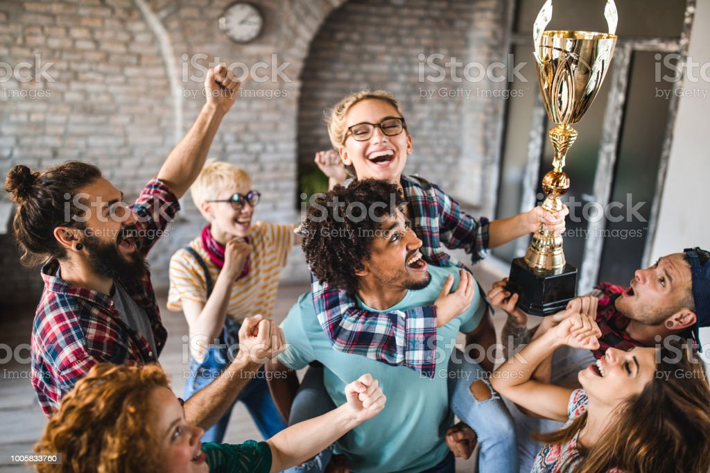 Large group of happy creative people celebrating getting a trophy at casual office. stock photo