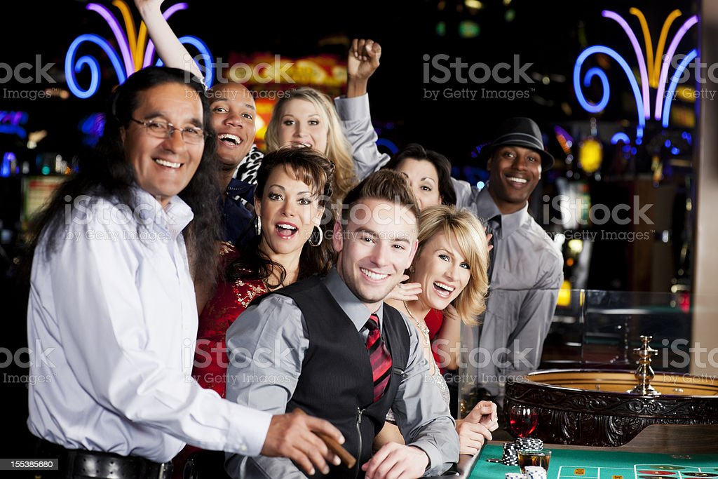 Large group of happy diverse people at the roulette table royalty-free stock photo