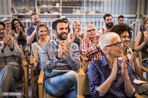 894290604 istock photo Large group of happy entrepreneurs applauding on a business seminar in a board room. 1091695068