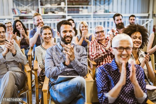 894290604 istock photo Large group of happy entrepreneurs applauding on a business seminar in a board room. 1140744530
