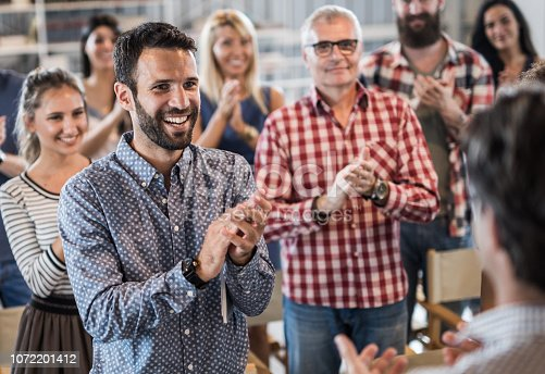 894290604 istock photo Large group of happy entrepreneurs applauding their colleague on a seminar. 1072201412