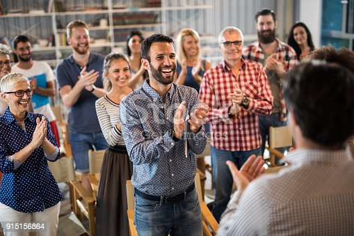 894290604 istock photo Large group of happy entrepreneurs applauding their colleague on a seminar. 915156864